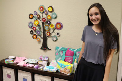 Young girl smiles with donated items for young mothers