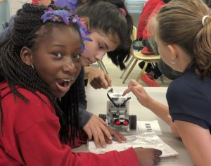 Young girl smiles while she and other girls program a robot