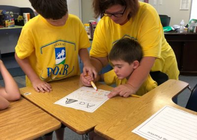 Teacher helping a boy learn to write while another boy watches